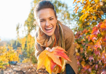 Laughing young woman holding colorful autumn leafs in city park Stock Photo