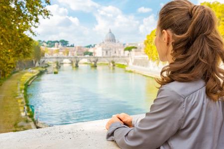後ろから見た、ポニーテールの髪を持つ女性は、テベレ川を渡って見えます。遠くには、サンピエトロ大聖堂を参照してください。