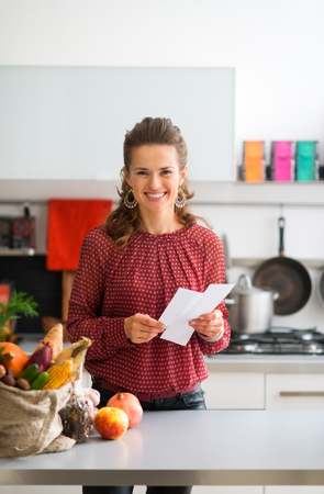 An elegant woman is looking up from her shopping lists, smiling happily. On the kitchen counter, a burlap sac holds a variety of fresh autumn fruits and vegetables.