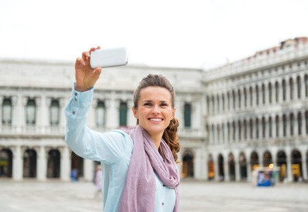 procuratie: A relaxed, elegant woman tourist is taking one of many photos on St. Marks Square. She is happy to see the Square almost empty of any other tourists. Stock Photo