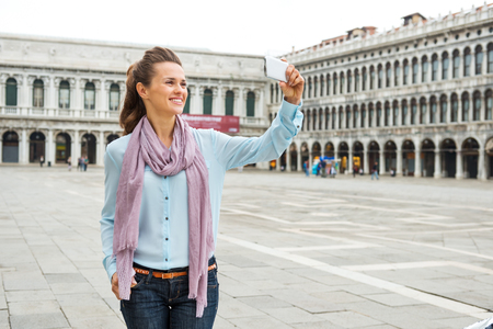 vecchie: A relaxed, elegant woman tourist holds her device up to take a photo while on St. Marks Square