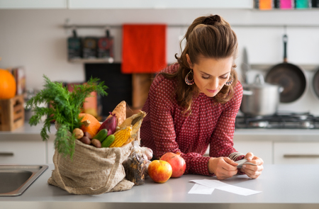 a kitchen: An elegant woman is reading the shopping lists on her kitchen counter. Next to her on the kitchen counter, a burlap sac holds a wide variety of fall fruits and vegetables.