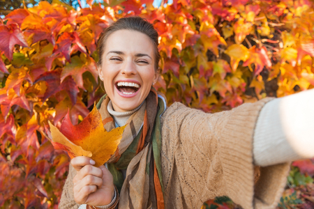 Portrait of cheerful young woman with autumn leafs in front of foliage making selfie Stockfoto