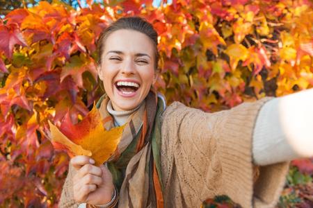Retrato de mujer joven alegre con las hojas del otoño frente a la toma de follaje selfie