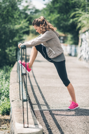 guardrail: An athletic woman leans against an urban guardrail, stretching out her legs after a long run. Her pink running shoes add a pop of colour.