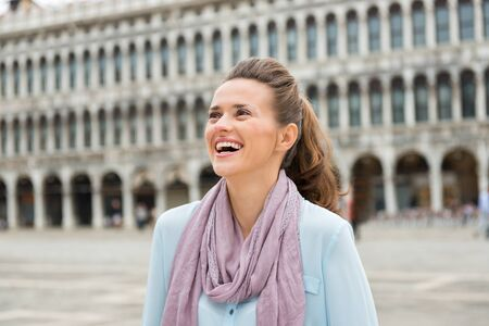 vecchie: Enthralled by the feeling of having St. Marks Square all to herself, a happy woman tourist loves the feeling of being there virtually alone. Stock Photo