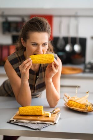 leaning on elbows: Looking off into the distance, a woman is leaning with her elbows on the kitchen counter as she takes her first bite into a freshly-cooked corncob, slathered with butter. Delicious...