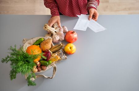burlap sac: Seen from above, a burlap sac is full of fresh fall fruits and vegetables. A womans elegant hands hold a bunch of fresh garlic and her shopping lists. Stock Photo