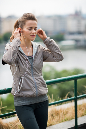 stride: Find that beat, find that motivation... A woman holds her earbuds into her ears, eyes closed, and lost in the rhythm of her music. Waiting for just the right beat to hit her stride while running.
