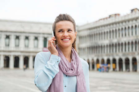 vecchie: Thank goodness for mobile phones. They make sharing the magic beauty of an empty St. Marks Square absolutely magic. Here, an elegant woman tourist chats on her mobile phone with friends.