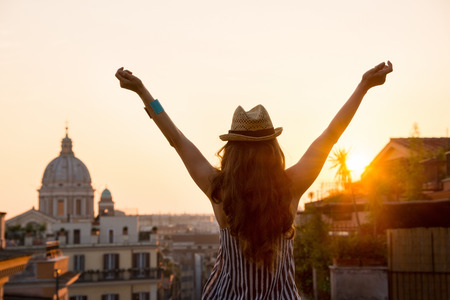 Seen from behind, a woman is standing with outstretched arms, looking out at the city of Rome at sunset in summer. Stockfoto