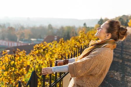 Portret van bruinharige vrouw in gebreid vest ontspannen in de herfst buitenshuis