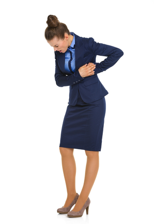 business costume: A businesswoman holds her side in pain, on her upper body, holding her rib cage while looking down, eyes closed, and working through the pain.