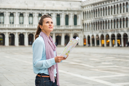 procuratie: Perhaps shes looking at the Belltower, or perhaps at the Doges Palace. But whichever way she decides to go, this elegant woman tourist knows it will be a feast for the eyes.