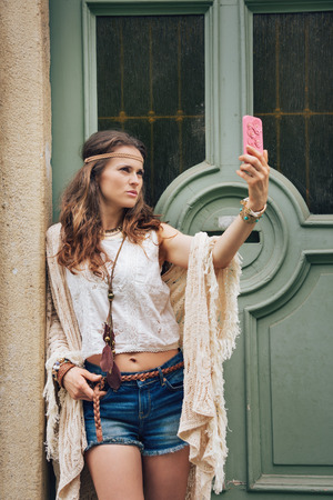 chic woman: Portrait of hippie woman in boho chic clothes standing outdoors against wooden door in old town and making selfie