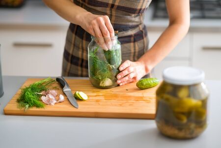 pickling: Step by step, the flavors come together. Here, a womans hands are hard at work, stuffing cucumbers and dill into a pickling jar as she prepares home-made dill pickles.