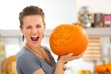 scaring: Portrait of young woman scaring with big Halloween pumpkin Jack-O-Lantern. Traditional autumn holiday