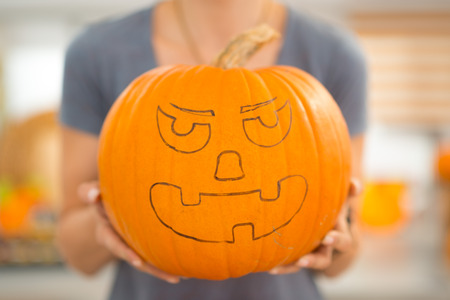 Closeup on big scary pumpkin Jack-O-Lantern for Halloween party in womans hands. Traditional autumn holiday