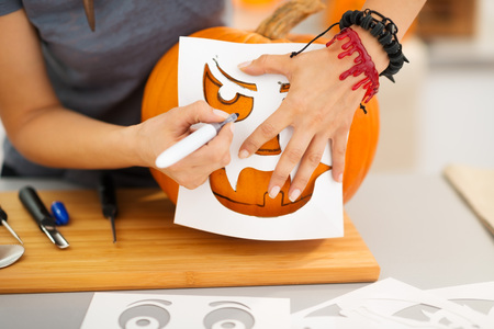jack: Closeup on woman using stencils to carve big orange pumpkin Jack-O-Lantern for Halloween party. Traditional autumn holiday