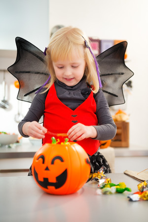 interested: Interested girl in bat costume checking halloween candy in decorated kitchen.  Halloween Candy is so good. Traditional autumn holiday