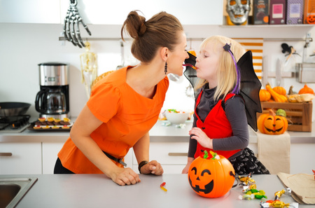 Funny young mother with daughter in bat costume eating colorfull halloween candy in decorated kitchen. Halloween Candy is so good. Traditional autumn holiday Stock Photo