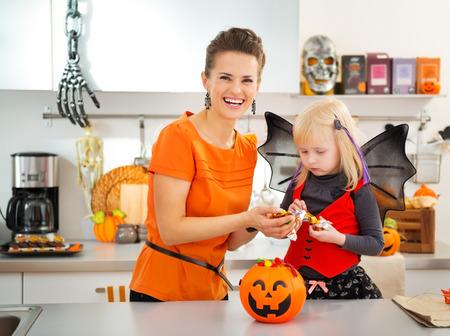 mama e hija: Muchacha rubia en traje de murciélago comer colorfull dulces de Halloween mientras que pasar tiempo con la madre en la cocina decorada. Caramelo de Halloween es tan bueno. Fiesta tradicional de otoño Foto de archivo