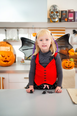 interested: Interested blond girl in halloween bat costume in decorated kitchen. Traditional autumn holiday