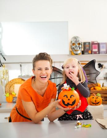 Gelukkige jonge moeder met dochter in knuppelkostuum eten colorfull halloween snoep in ingerichte keuken. Halloween Candy is zo goed. Traditionele herfstvakantie