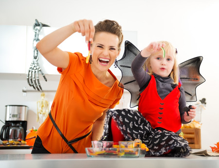 Halloween dressed baby girl with young cheerful mother showing colorful gummy worm candies in decorated kitchen.  Halloween Candy is so good. Traditional autumn holiday