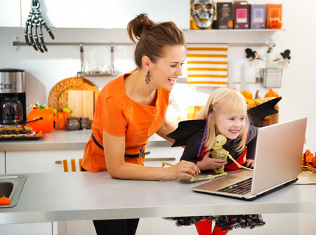 Portrait of happy mother with daughter in halloween bat costume having video chat on laptop with friends in decorated kitchen. Traditional autumn holiday Archivio Fotografico