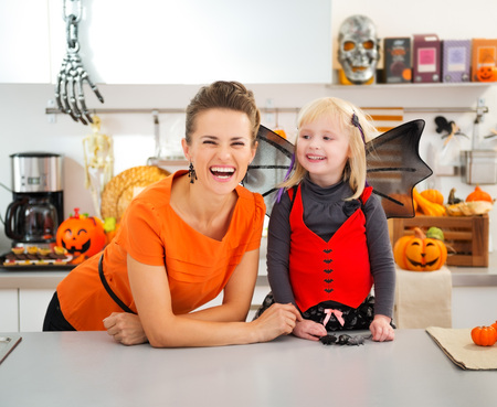 holiday spending: Funny blond girl in halloween bat costume spending time with mother in decorated kitchen. Traditional autumn holiday Stock Photo