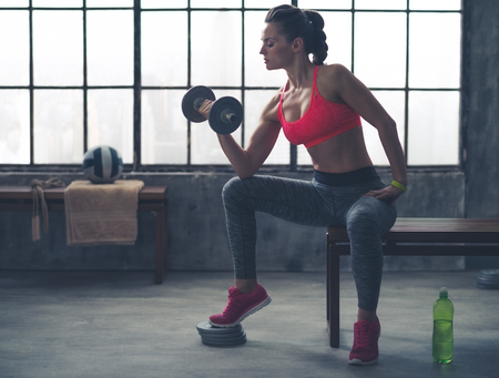 profile: Feel that burn! A fit, sporty young woman is sitting in profile on a bench in profile, lifting weights with one hand, while resting her elbow on her knee.