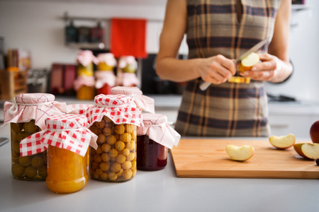 storing: Jars of freshly-preserved fruits are standing on a counter, ready to be put away for the winter. In the background, an elegant woman is quartering more apples.