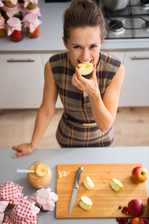quartered: Seen from above, a happy woman smiles as she is biting into a freshly-cut apple. On the kitchen counter, a wooden cutting board with quartered apples.
