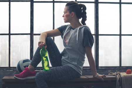 gym room: Having had a good workout, a fit, healthy woman takes a few moments to relax and look out at the city below while sitting on a bench holding her water bottle. Next to her, a ball and towel.