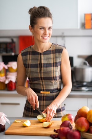 preserves: An elegant woman is standing in her kitchen, preparing apples to use to make applesauce and other fruit preserves. With a dash of cinnamon, the outcome will be delicious. Stock Photo
