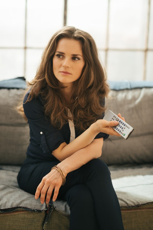 loft living: Pensive elegant brunette woman with TV remote control in hand relaxing on  sofa in loft living room. Modern lifestyle concept.