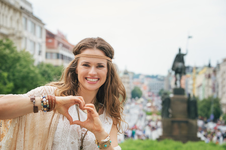 shaped hands: Brunette bohemian woman tourist standing on Wenceslas Square in Prague and showing heart shaped hands. In the background Saint Wenceslas statue on Wenceslas Square in Prague. Tourism travel concept.