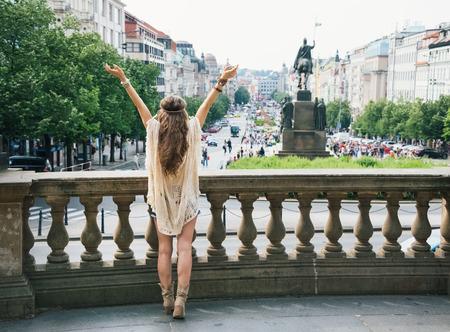 後ろから見た、ラフコリー ヒッピー探して女性観光はそうに立って両手を広げて、プラハ、ヴァーツラフ広場の聖ヴァーツラフ像。観光旅行の概念 写真素材