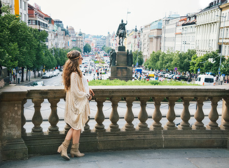 czech women: Longhaired bohemian woman tourist in knitted shawl standing on Wenceslas Squarein in Prague. In the background Saint Wenceslas statue in Prague. Tourism travel concept. Stock Photo