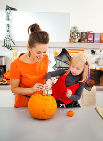 Happy mother with halloween dressed daughter using stencils to prepare for carve big orange pumpkin Jack-O-Lantern in decorated kitchen. Traditional autumn holiday