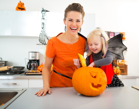 mam: Happy halloween dressed girl with young mother in decorated kitchen preparing big orange pumpkin Jack-O-Lantern for party. Traditional autumn holiday