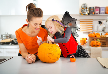 Young mother with daughter in bat costume creating big orange pumpkin Jack-O-Lantern on Halloween party in decorated kitchen. Traditional autumn holiday Banco de Imagens