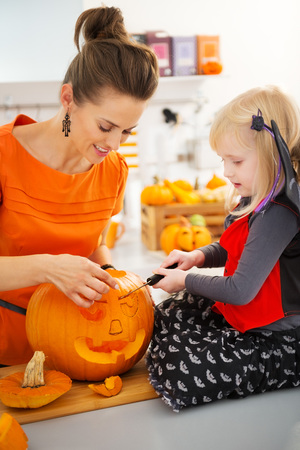 Smiling mother with daughter in bat costume carving big orange pumpkin Jack-O-Lantern for Halloween party in decorated kitchen. Traditional autumn holiday