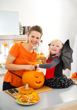 Happy mother with halloween dressed daughter carving big orange pumpkin Jack-O-Lantern in decorated kitchen. Traditional autumn holiday