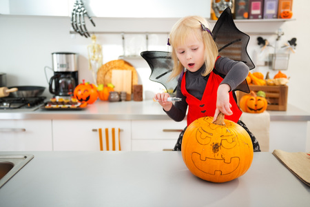 interested: Interested blond girl in bat costume using stencils to carve big orange pumpkin Jack-O-Lantern on Halloween party in decorated kitchen. Traditional autumn holiday