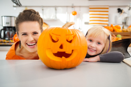 Funny modern mother with daughter in bat costume looking out from big orange pumpkin Jack-O-Lantern in Halloween decorated kitchen. Traditional autumn holiday