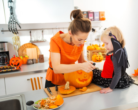 Young mother with daughter in bat costume carving big orange pumpkin Jack-O-Lantern for Halloween party in decorated kitchen. Traditional autumn holiday