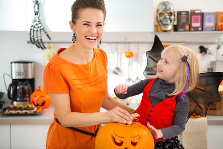 Happy blond girl in bat costume with mother in Halloween decorated kitchen preparing big orange pumpkin Jack-O-Lantern for party. Traditional autumn holiday