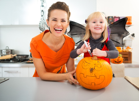 Ð¡heerful mother with halloween dressed daughter creating big orange pumpkin Jack-O-Lantern in decorated kitchen. Traditional autumn holiday Banco de Imagens